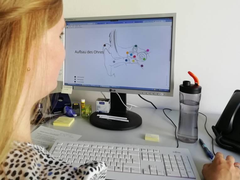 Dame mit langen Haaren sitzt am Schreibtisch vor einem PC
