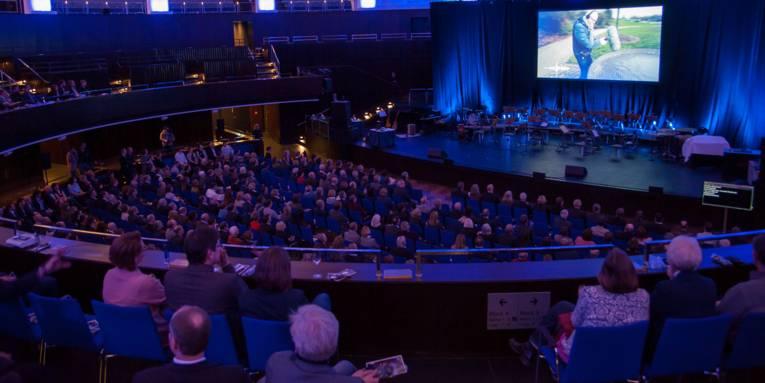 Publikum in einem großen Veranstaltungssaal mit mehreren Reihen und Rängen. Die Gäste schauen in Richtung Bühne, auf der über eine Leinwand ein Film abgespielt wird.