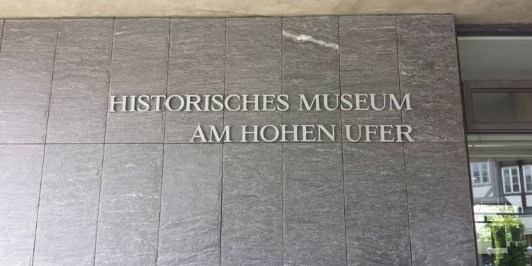 """Dieses Bild zeigt den Namen des Museums am Eingang. Es steht geschrieben """"Historisches Museum Am Hohen Ufer""""."""