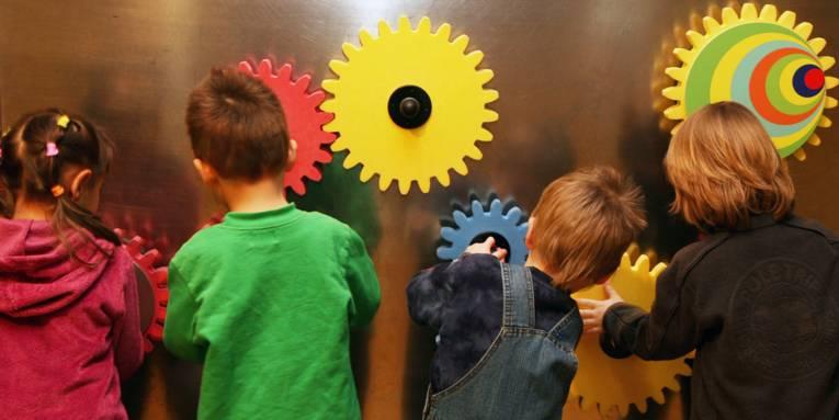 Vier Kinder sind von hinten zu sehen. Sie sind aktiv an einer Magnet-Zahrradwand.