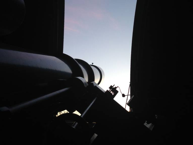 Ein Teleskop, mit dem Beobachtungen durchgeführt werden. In der Mitte des Bildes ist ein Abspielsymbol abgebildet.