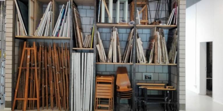 Zeigt gesammelte Werke auf Leinwand und alles, was u. a. zum Malen auf Leinwand benötigt wird wie z. B. Staffelei, Leinwände, Stühle, Hocker, kleine Tische.