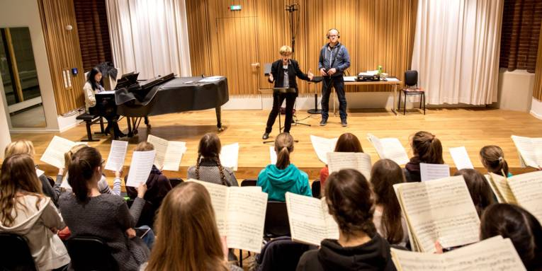 Eine Mädchenchorgruppe sitzt mit Notenblättern auf Stühlen vor einer Bühne und singt. Auf der Bühne befinden sich ein Mädchen, das Klavier spielt, eine Chorleitern, die dirigiert und ein Mann, der Tonaufnahmen macht.