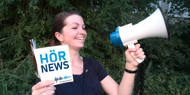 """Eine Dame hält ein Heft mit der Aufschrift """"Hörnews"""" in der Hand und ruft etwas in Richtung eines Megafons"""