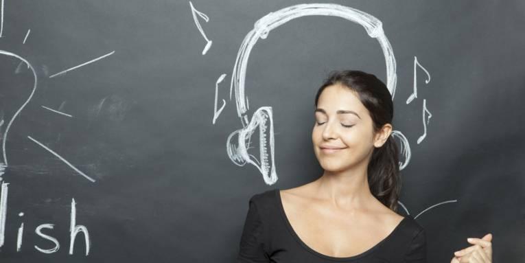 Eine Frau steht mit geschlossenen Augen vor einer Tafel und sie sieht aus als würde sie sich zu Musik bewegen. Auf die Tafel ist auf Höhe ihres Kopfes ein Kopfhörer mit Kreide gezeichnet.