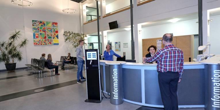 Ein Empfang mit einem Wartebereich im Hintergrund. Menschen am Tresen, am Telefon und im Wartebereich sitzend sind zu sehen.