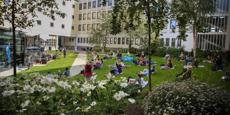 Eine Bühne in einem Innenhof zwischen hohen Gebäuden. Vor der Bühne sitzen Menschen auf dem Rasen. Im Vordergrund blühende Büsche.