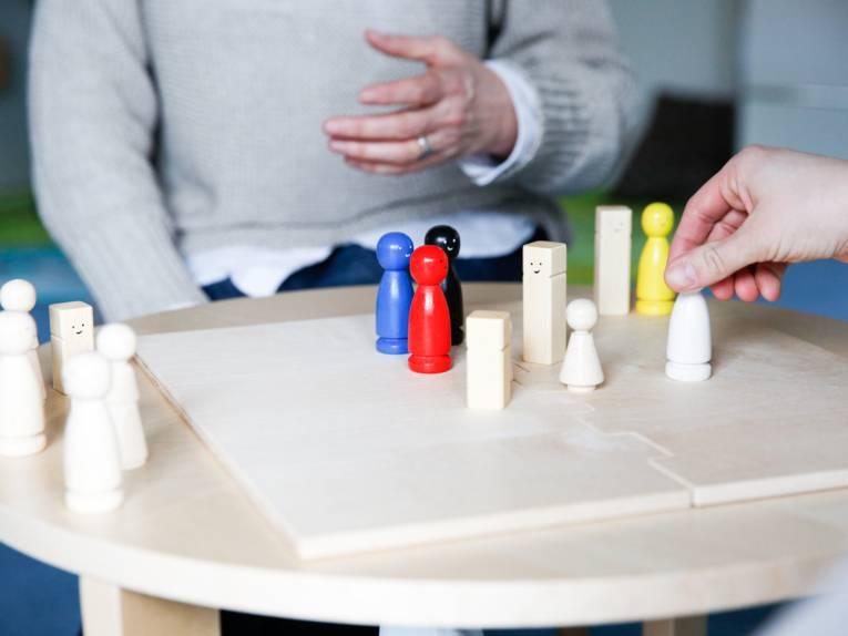 Ein Brettspiel mit verschiedenfarbigen Holzfiguren auf einem runden Tisch, eine Hand bewegt eine Holzfigur.