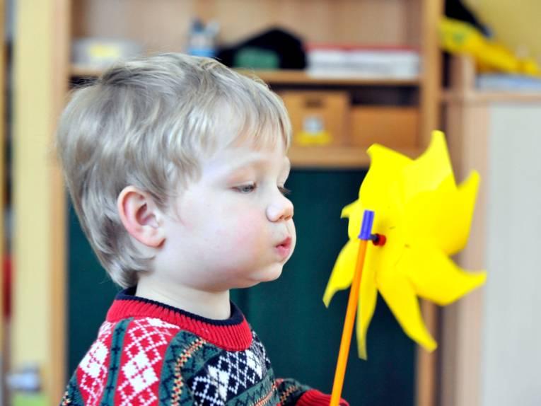 Ein Junge pustet gegen ein Windspiel, es dreht sich.