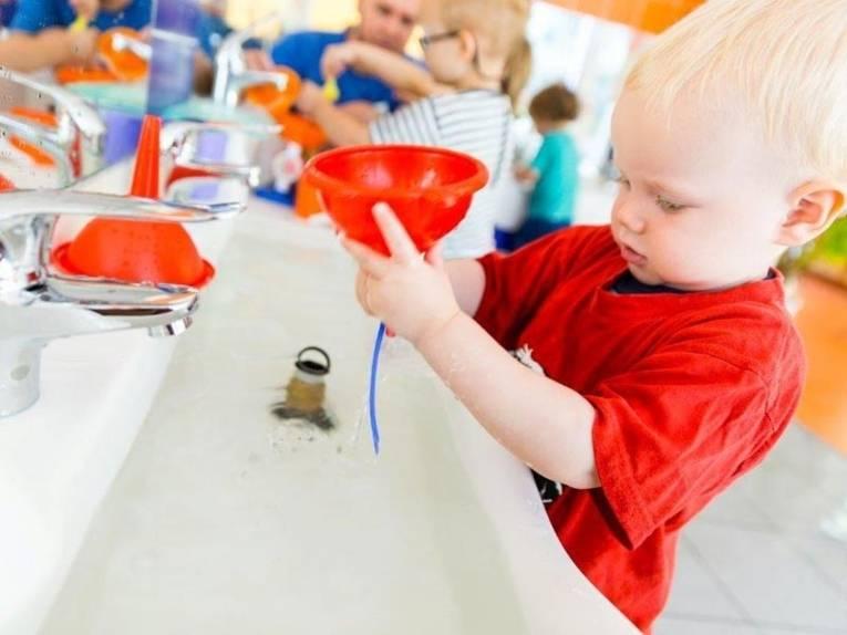 Ein Krippenkind mit einem Trichter an einem Wachbecken.