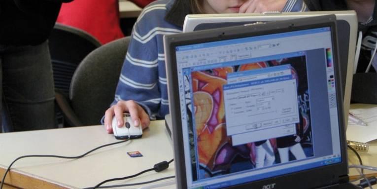 Blick auf einen eingeschaltete Computermonitor und Personen im Raum.