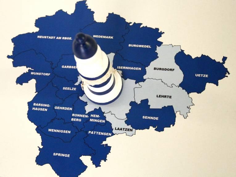 Ein kleiner Leuchtturm steht auf einer Karte der Region Hannover, die Kommunen sind beschriftet.