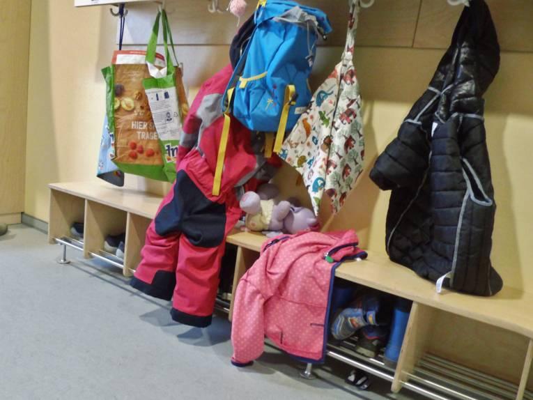 Garderobe mit Rucksäcken, Taschen, Jacken und weiteren Kleidungsstücken.