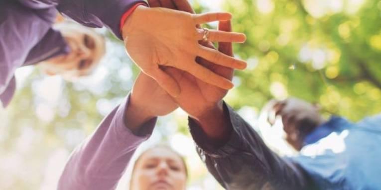 Drei Personen legen ihre Hände aufeinander, die Hände sind von unten forografiert.