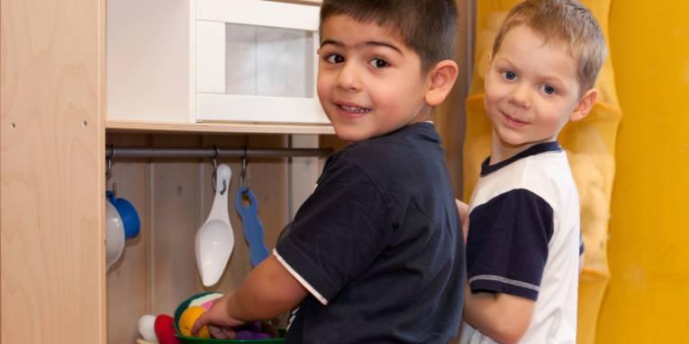 Zwei Jungen spielen in einer Spielküche