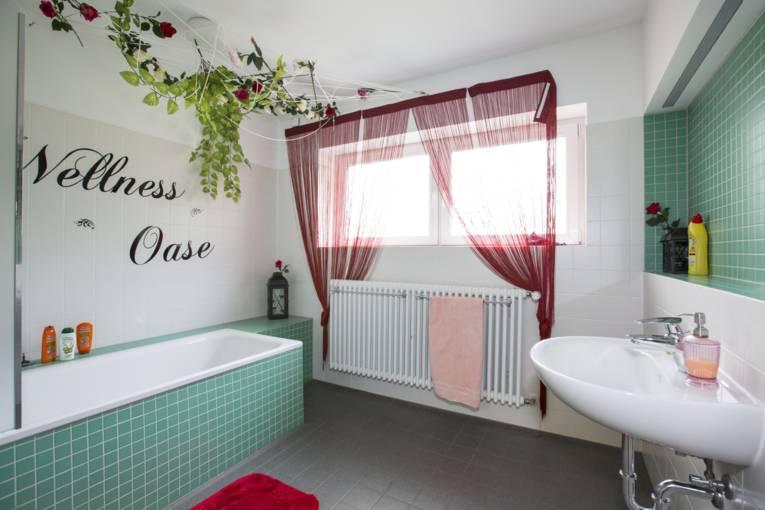 """Badezimmer mit türkis gefliester Badewanne und dunklen Fußbodenfliesen. An einer Wand steht """"Wellness Oase"""" geschrieben und Rosen sind aufgemalt. In zwei Ecken sind Rosen als Dekoration aufgestellt. Auf dem Waschbecken steht ein Seifenspender, auf der Ablage über dem Waschbecken ein Reinigungsmittel und bei der Badewanne befinden sich Schampoo, Duschgel und Spülung. Auf dem Boden und auf der Heizung liegt jeweils ein Handtuch."""