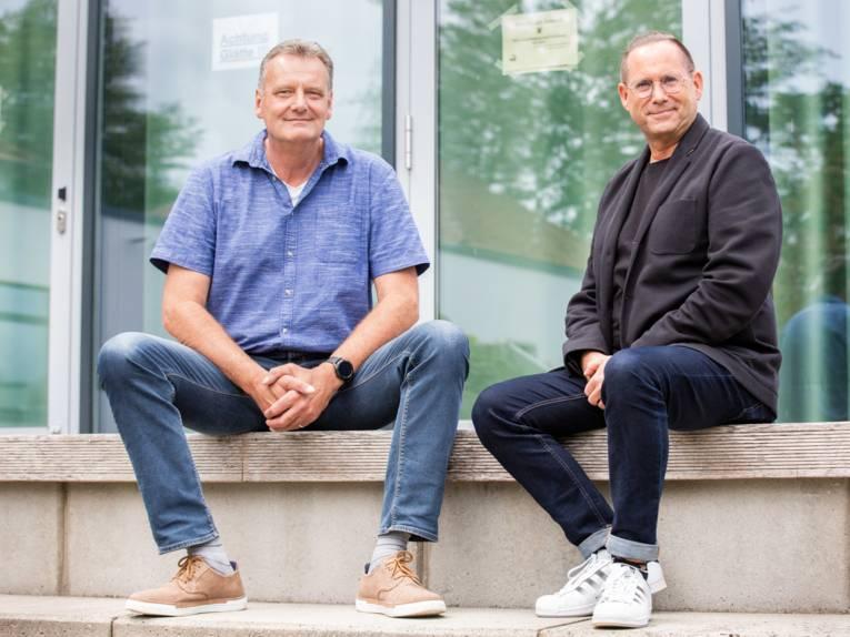 Zwei Männer sitzen unter freiem Himmel mit Abstand auf einer Treppe.