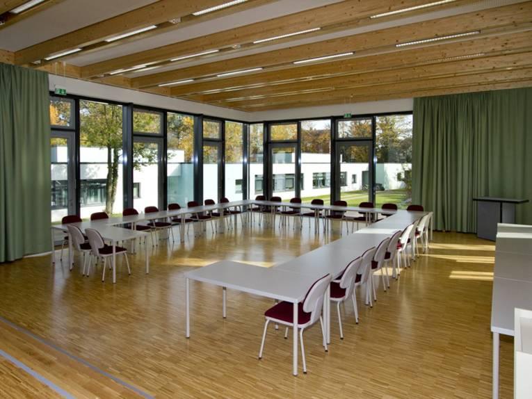 Ein saalähnlicher Raum mit hellem Holzfußboden und großer Fensterfront. In dem Raum stehen mehrere Tische und Stühle.