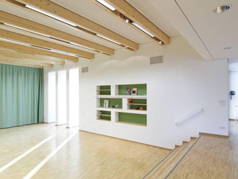 Ein saalähnlicher Raum mit hellem Holzfußboden und wenigen Stufen. In einer Wand sind sechs Regale, deren Rückwände grün gestrichen sind.