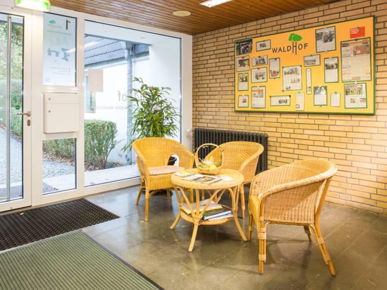 """Der Innenbereich eins Eingangs. Direkt neben der Tür ist ein Briefkasten angebracht. In dem Vorraum stehen Drei Korbstühle und ein dazu passender runder Tisch. An der wand dahinter ist eine Art Tafel angebracht, auf der """"Waldhof"""" geschrieben steht und die mit verschiedenen Zeitungsartikeln über den waldhof bestückt ist."""