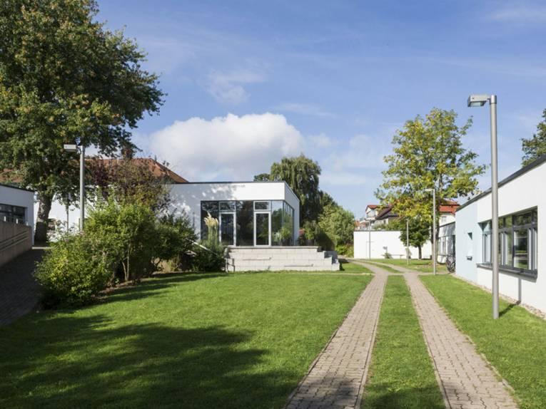Mehrere kleine, weiß verputzte Häuser mit Flachdach und dazwischen grüne Rasenfläche. Auf dem Gelände befinden sich außerdem mehrere Bäume und Straßenlaternen.