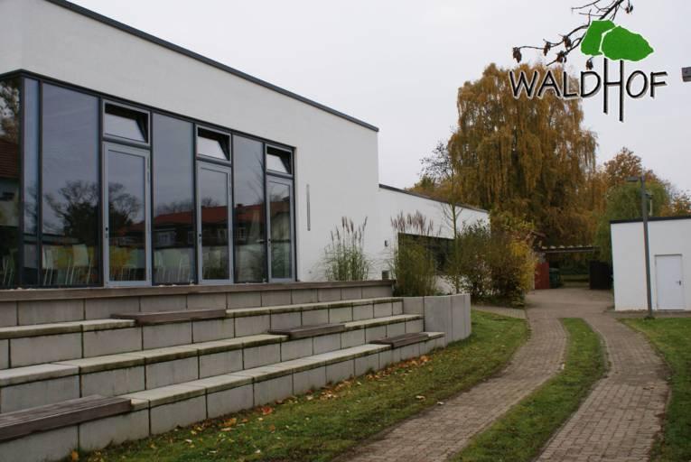 Ein weißes Gebäude mit Flachdach. Davor sind Treppenstufen, die so breit sind wie das Gebäude an sich und als Sitzbänke (Tribüne) verwendet werden können.