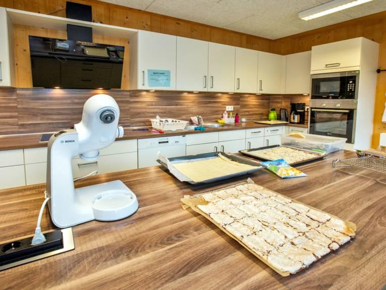 Küche mit Arbeitsfläche und Küchenmaschine, Speisen liegen auf Backblechen.