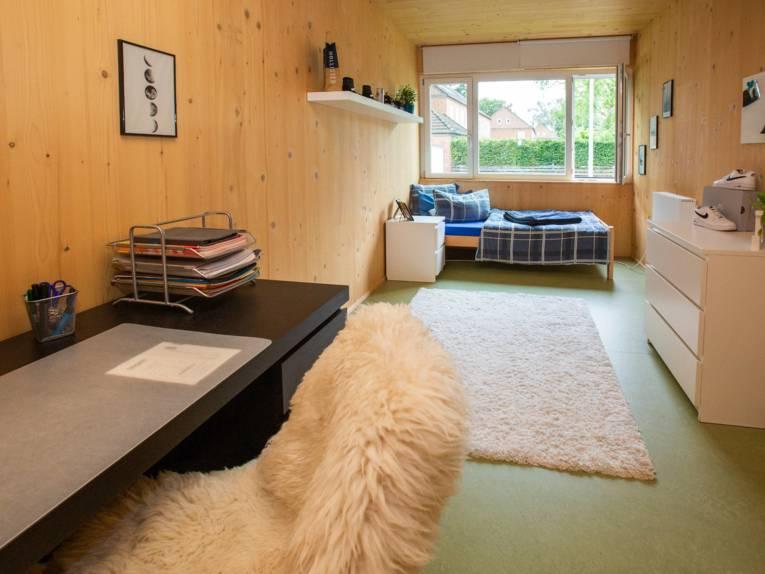 Jugendzimmer mit Bett, Schreibtisch und Stauraum.