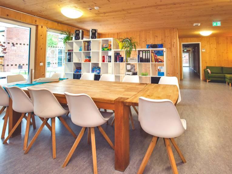 Esszimmer mit Esstisch, Stühlen und einer Medienwand im Hintergrund.