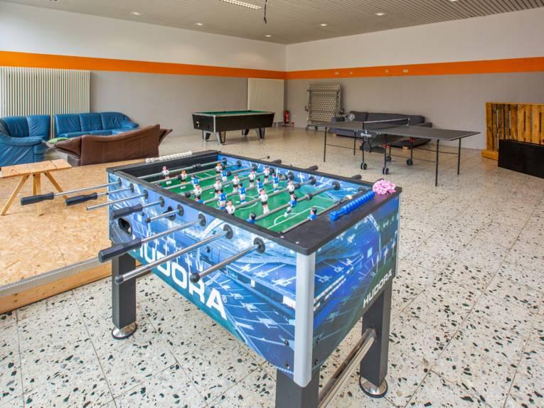 Großer Raum mit Sofas, Kicker-Tischfußball, Tischtennisplatte, Billard und mehr.