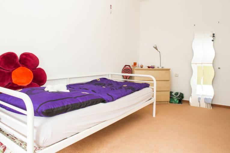 Ein Jugendzimmer mit einem Bett, auf dem eine Bettdecke, ein Kopfkissen und ein Blumenkissen liegen. An die Wand ist ein Spiegel gelehnt und daneben steht eine Kommode.