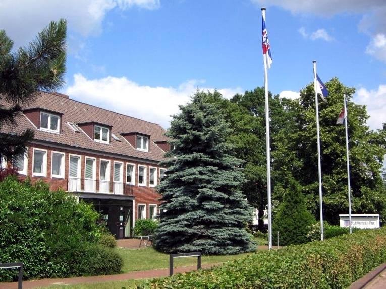 Vor einem Gebäude mit roter Klinkerfassade stehen mehrere Bäume und drei beflaggte Fahnenmasten.