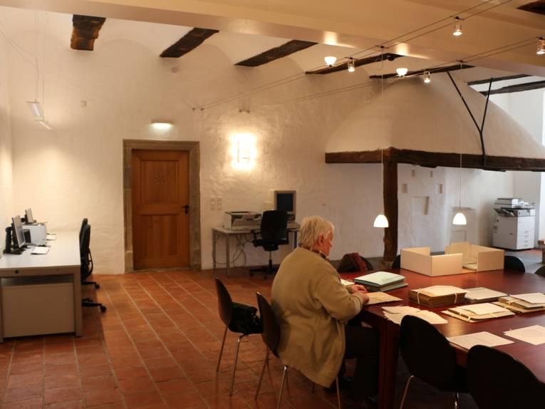 Ein Mann sitzt an einem großen Tisch, auf dem viele Blätter bzw. Dokumente verteilt liegen.