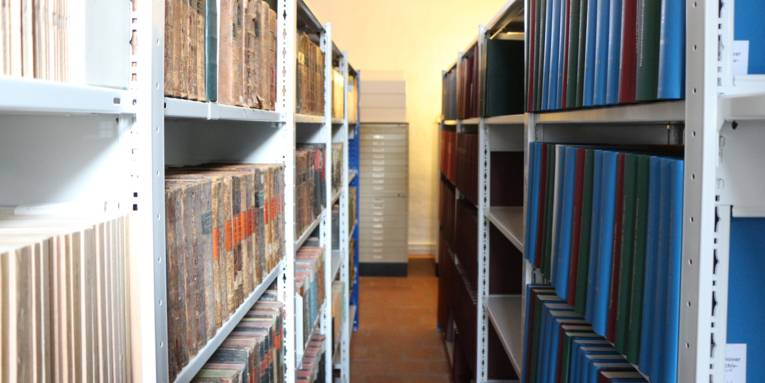Zwei Regalreihen mit Büchern und Ordner und dazwischen ein Durchgang.