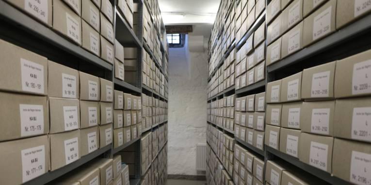Hunderte gleichgroße Kartons verstaut in Regalen. Zwischen den beiden Regalreihen ist ein Durchgang.