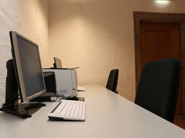 Zwei nebeinander stehende Schreibtische mit Schreibtischstuhl, auf denen sich jeweils ein Monitor und eine Tastatur befinden. Zwischen den beiden Bildschirmen ist ein drucker platziert.