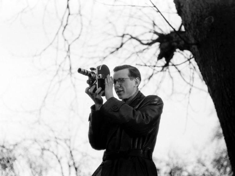 Ein Mann im Ledermantel und mit Brille steht draußen neben einem Baum und fotografiert mit einer Kamera.