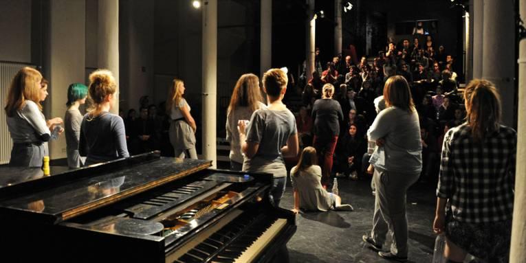 Ein Klavier und mehrere Mädchen auf einer Theaterbühne. Der Blick geht von der Bühne in Richtung Publikum - die Schauspielerinnen sind von hinten und die Zuschauer von vorne zu sehen.