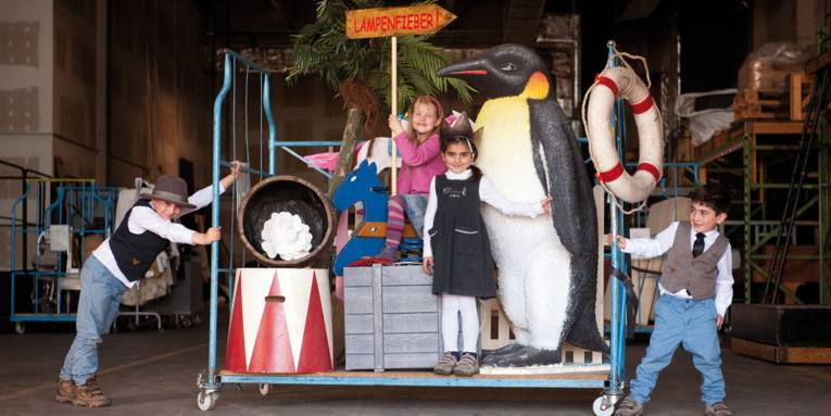Zwei kleine Jungs rechts und links von einem Rollwagen. Auf dem Rollwagen befinden sich zwei kleine Mädchen und Teile einer Bühnenkulisse (u. a. ein riesiger Pinguin und ein Schaukelpferd).