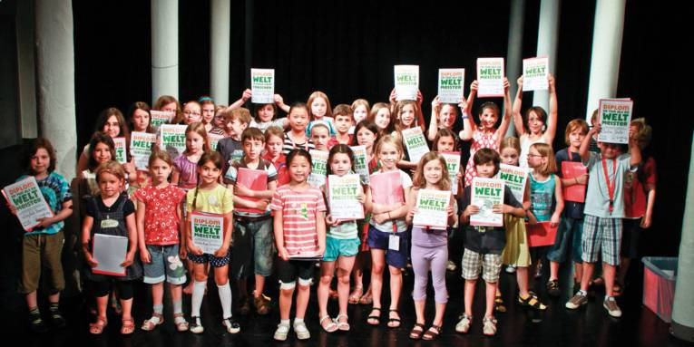 """Etwa vierzig Mädchen und Jungen auf einer Bühne. Einige von ihnen halten eine Urkunde in die Kamera auf der """"DIPLOM SO TUN ALS OB WELT MEISTER"""" steht."""
