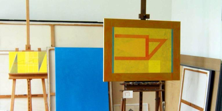 Zwei abstrakte Bilder stehen auf Staffeleien, weitere Bilder und unbemalte Leinwände lehnen an der weiß gestrichenen Wand.