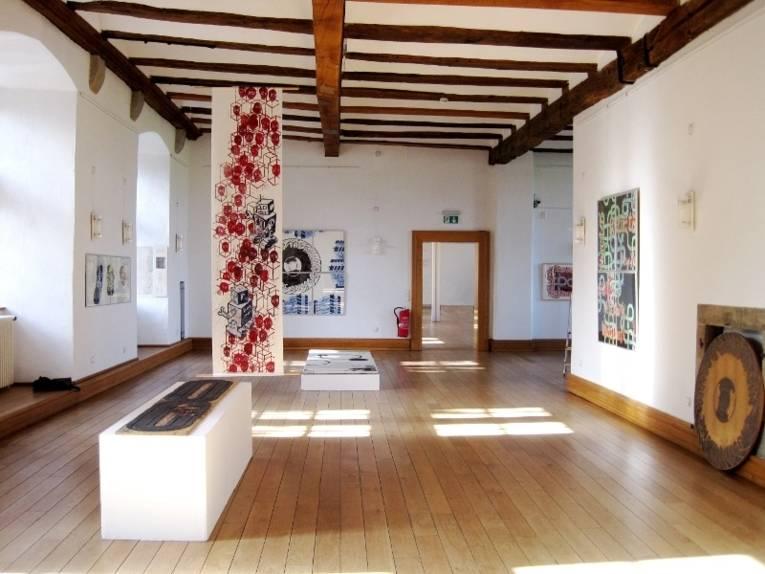 Kunst von Harald Schiel ist in einem Saal von Schloss Landestrost ausgestellt. Unter der Decke sind Holzbalken, die Wände sind weiß und der Fußboden besteht aus Parkett.