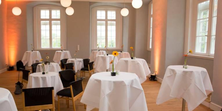 Ein Saal mit großen Fenstern, indem einige runde Stehtische sowie einige Tische mit Bestuhlung stehen. Auf allen Tischen ist eine weiße Tischdecke und einzelne Blumendekoration. Der raum wird durch mehrere kugelförmige Deckenlampen beleuchtet.