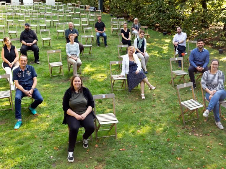 Acht Frauen und sechs Männer im Freien auf Klappstühlen. Es sind noch weitere, leere Klappstühle im Bild.