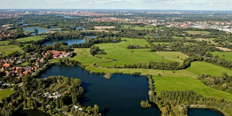 Luftaufnahme: Mehrere kleine Gewässer sind durch Gräben miteinander verbunden. Die Gewässer werden unterbrochen von Grünflcäehn, Bäumen und kleinen Siedlungen. Im Hintergrund ist die Stadt Hannover mit Maschsee und Fernsehturm zu erkennen.