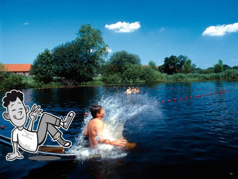 Ein Junge ist gerade von der Rutsche gerutscht und taucht ins aufspritzende Wasser ein.