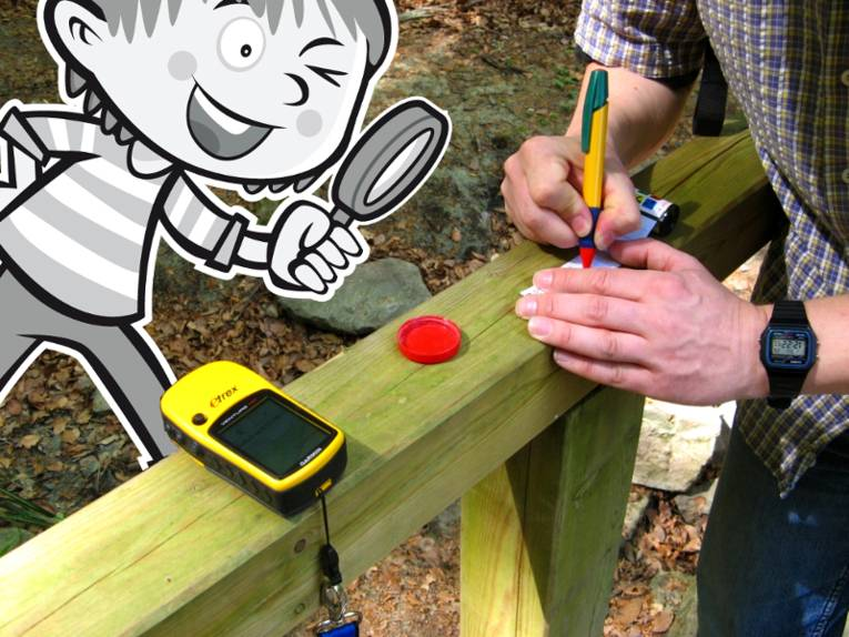 Ein GPS-Gerät liegt auf einem Holzgeländer. Eine Person schreibt Daten auf ein Stück Papier, das als Fundstück beim Geocaching versteckt wird. Eine gezeichnete Person schaut mit einer Lupe auf das Papier.