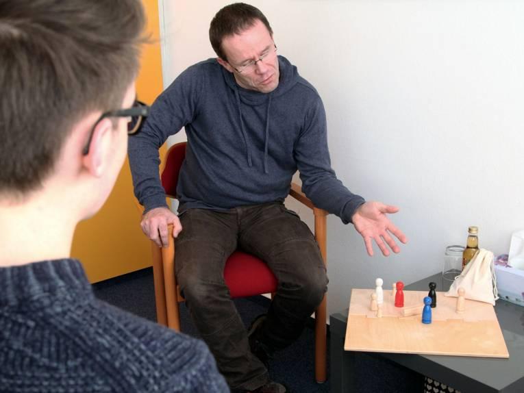 Ein Mann analysiert mit einem Jugendlichen mithilfe von Spielfiguren, welche Position bestimmte Personen zueinander einnehmen.