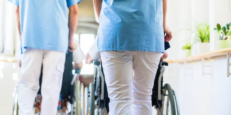 Pfleger, die Patienten im Rollstuhl über einen Flur schieben