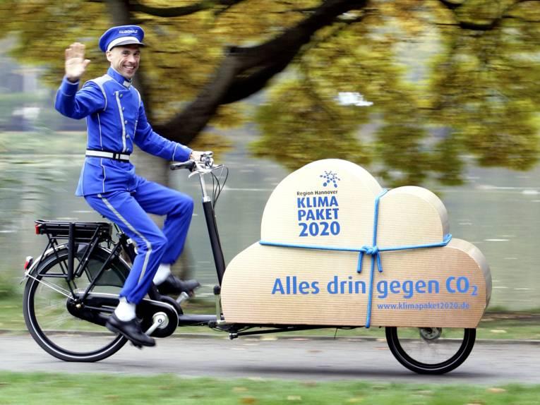 """Ein Mann trägt eine Dienstbotenuniform und fährt auf einem Lastenfahrrad. Auf der Ladefläche des Fahrrads ist eine braune Wolke in Paketform. Darauf steht """"Region Hannover. Klimapaket 2020. Alles drin gegen CO2 – www.klimapaket2020.de"""